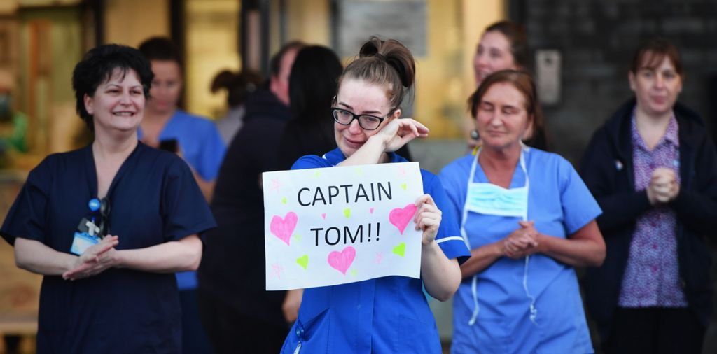 NHS staff in Liverpool clapping for key workers, with one holding a sign in support of Captain Tom Moore