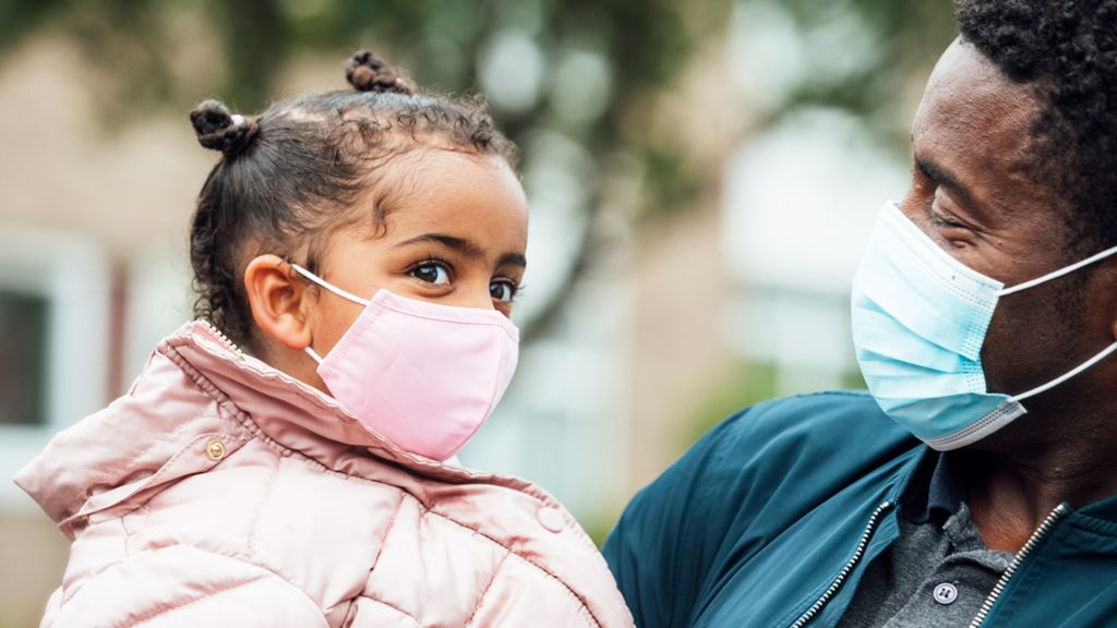 Father and daughter wearing masks
