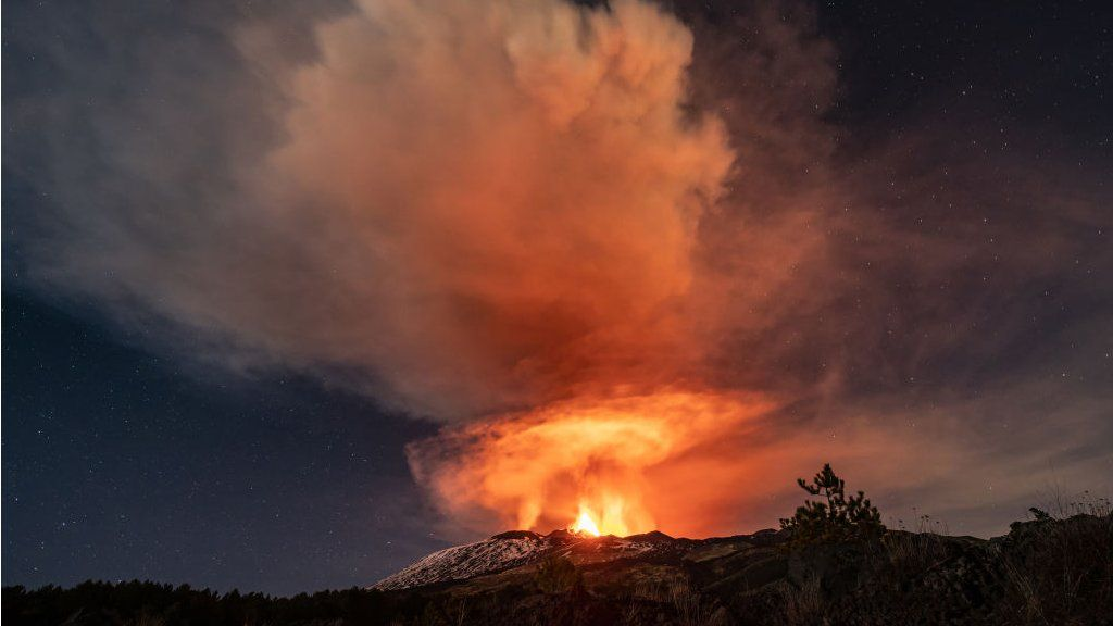 Mount Etna erupting at night