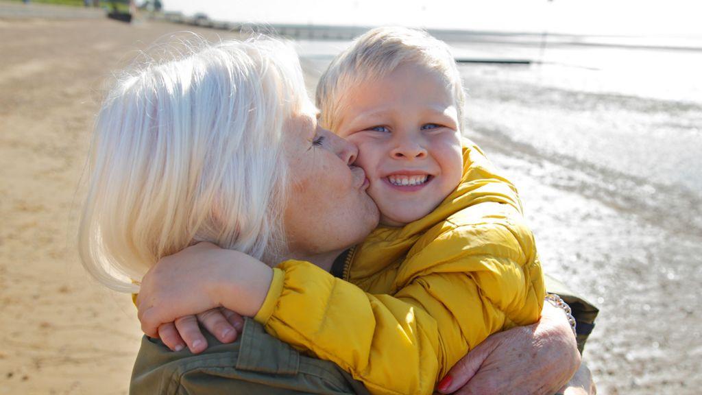 Grandmother hugging her grandson on a beach