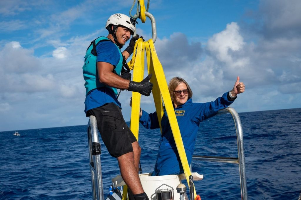 Kathy gives a thumbs up while on a ladder toward ocean