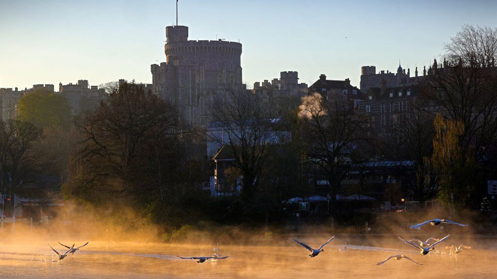 First light rises over Windsor Castle seen from across the River Thames