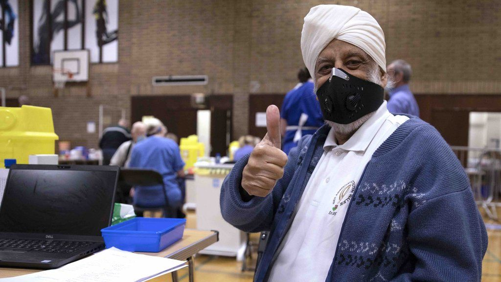 Sikh man gives a thumb-up after getting vaccinated in a sports centre