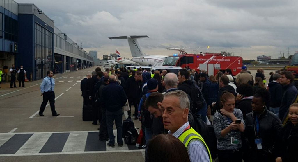 Passengers outside the terminal building and grounded flights at London City Airport
