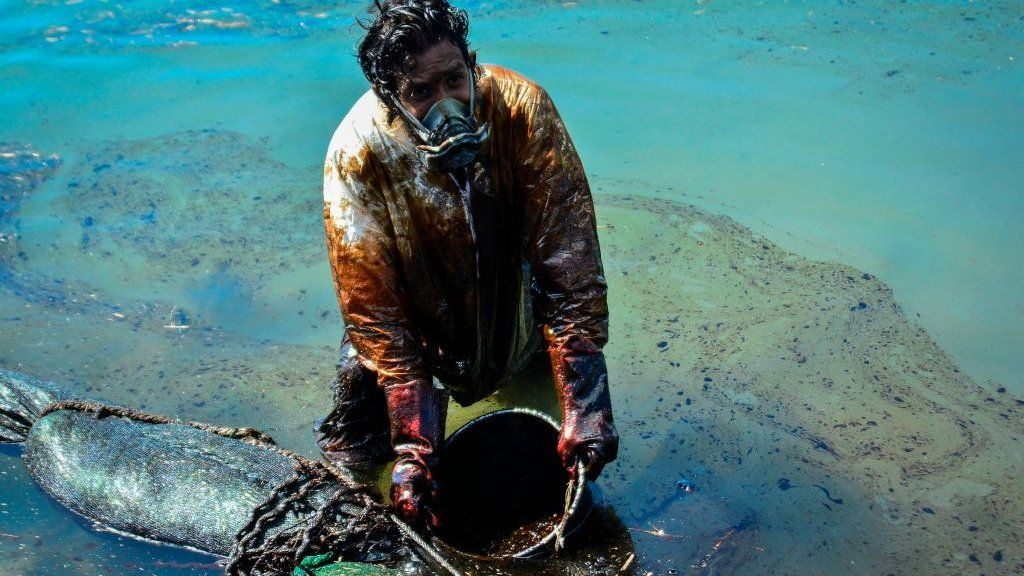 Man clearing oil slick from beach