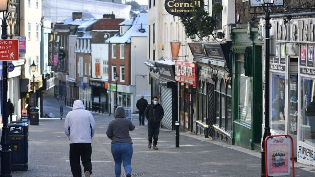 Pedestrians walk along a high street with the shops closed in Maidstone