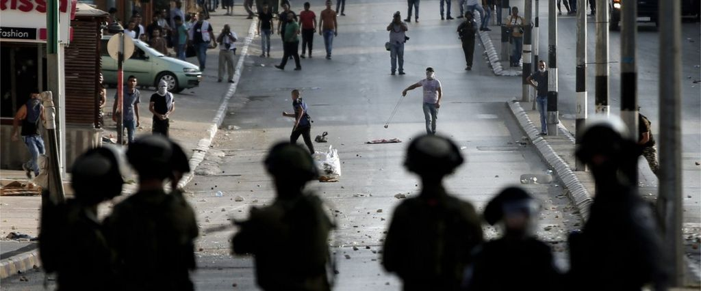 """Israeli soldiers stand guard in front of Palestinian stone throwers during clashes in the West Bank town of Bethlehem on October 5, 2015 after Israel""""s army shot dead a 13-year-old Palestinian."""
