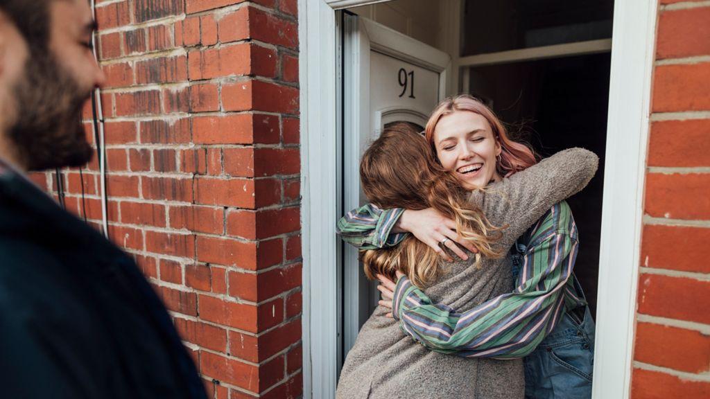 Two young women hugging