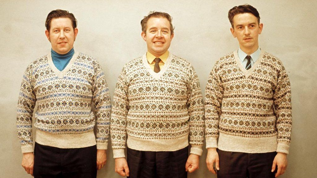 Three men pose wearing matching Fair Isle jumpers on one of the Shetland Islands in 1970