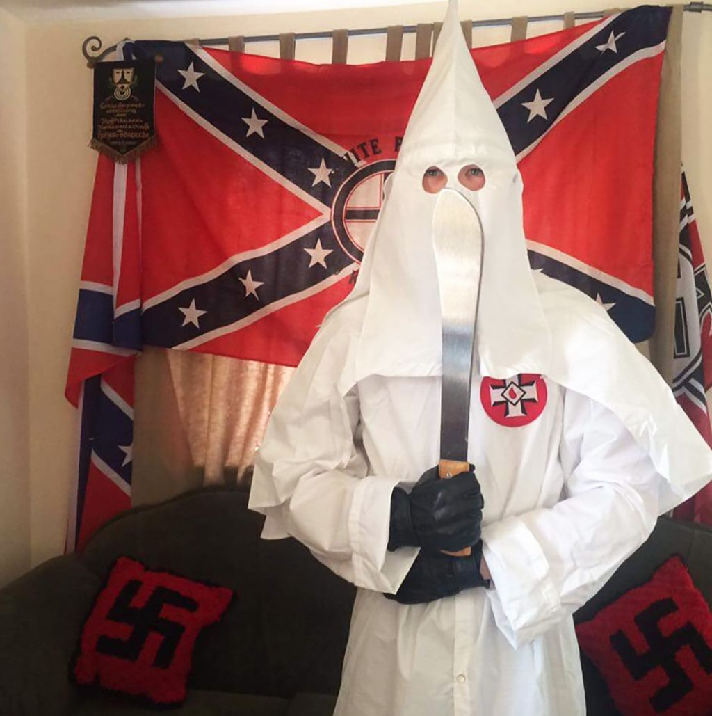 Adam Thomas in a KKK outfit, with large knife