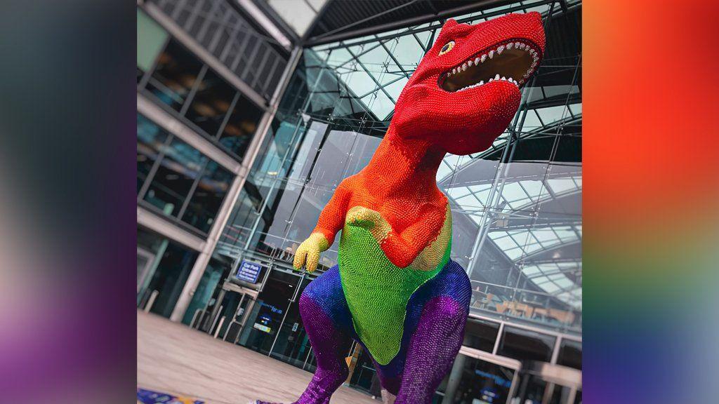 Dinosaur sculpture in Pride colours