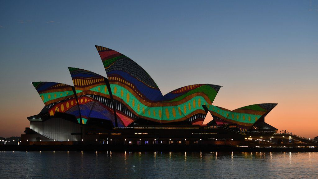 The sails of the Sydney Opera House are lit up at dawn with an artwork by Indigenous artist Frances Belle-Parker