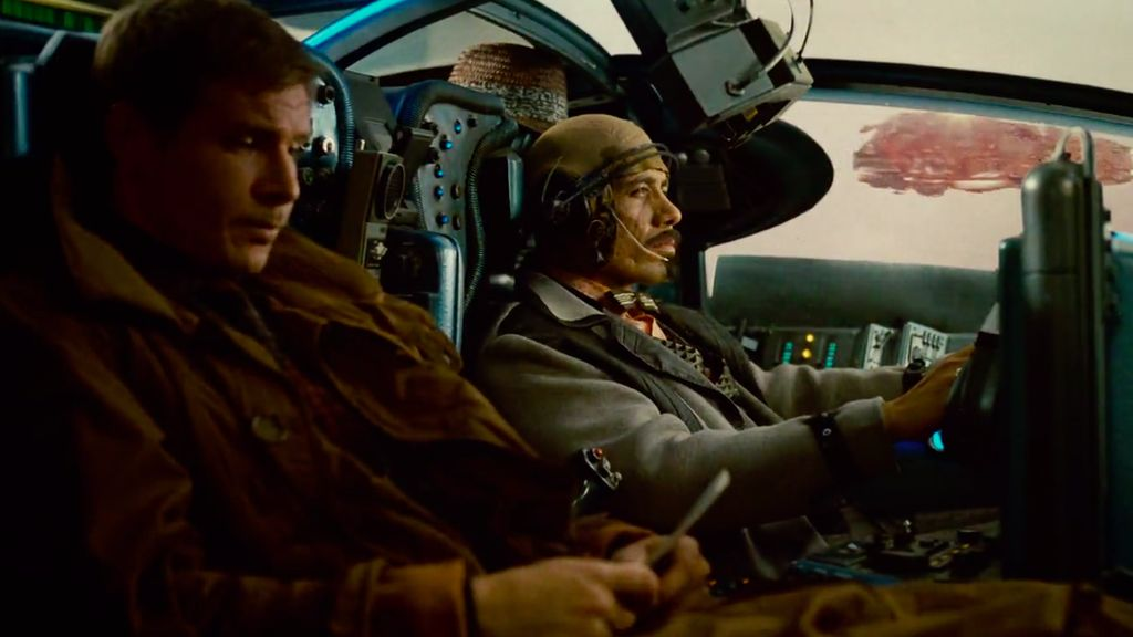 Deckard sits with officer Gaff in a flying car