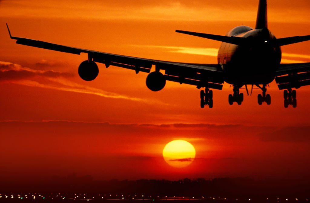 Boeing 747-400 landing on the runway at sunset with runway-lights on.