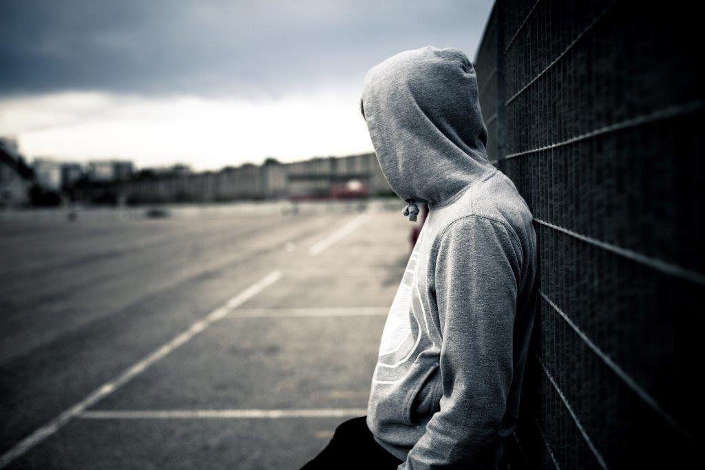 Teenager in hood leans on railing