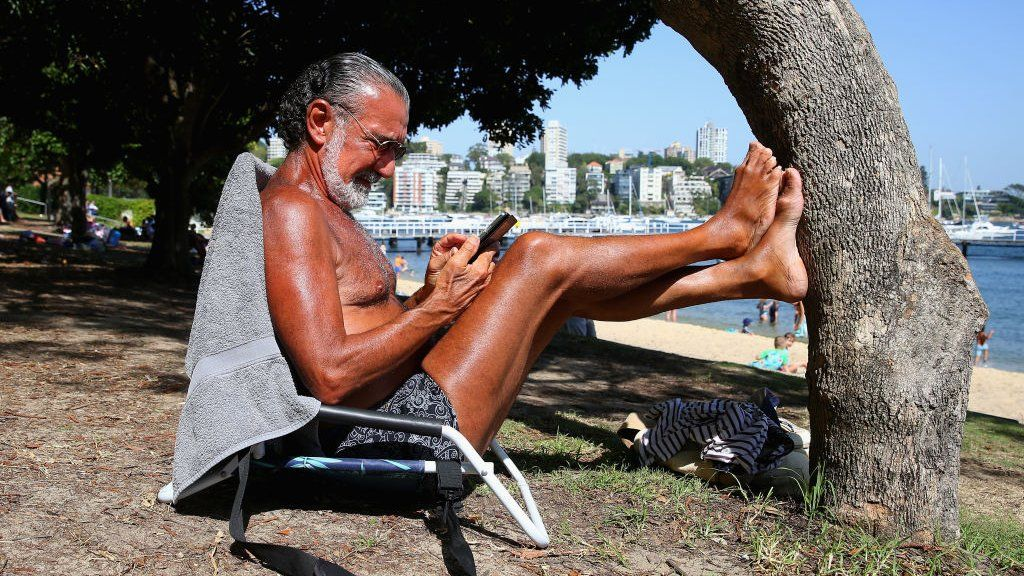 A beachgoer reads his phone in the sun in Sydney on Tuesday
