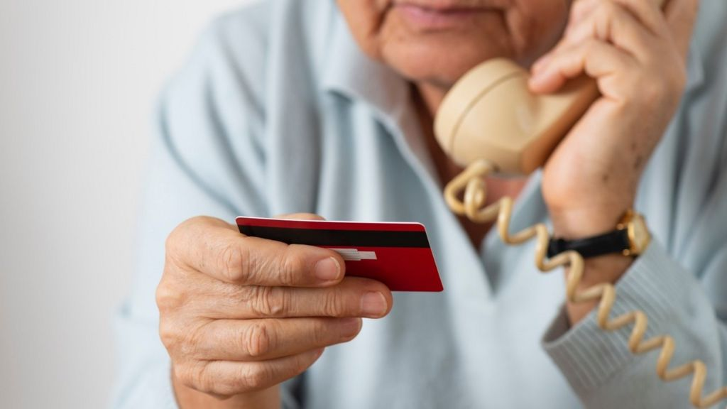 Person holding phone and credit card