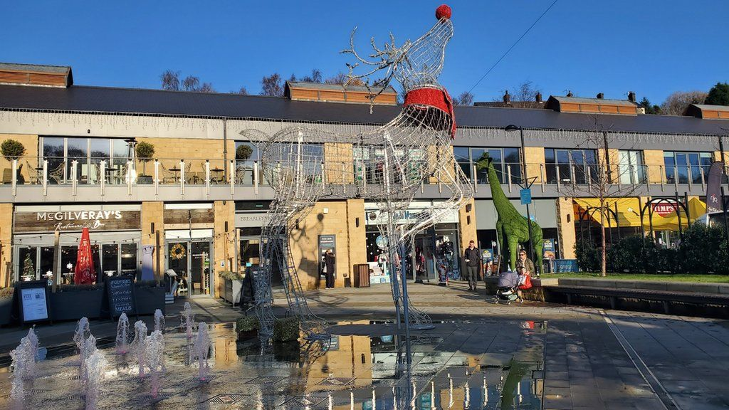 A shopping centre with a metal statue of a reindeer