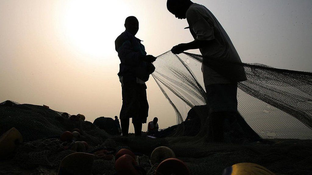 Fishermen prepare their fishing nets in Accra.