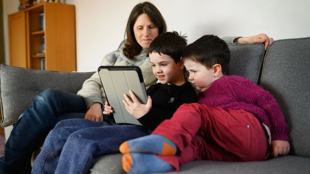 Two young children and their mother look at a tablet computer on a sofa