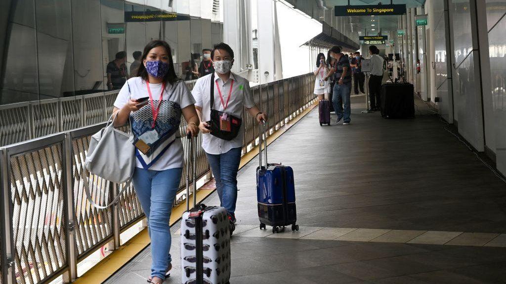 Пассажиры идут к круизному лайнеру World Dream, пришвартованному в круизном центре Marina Bay, перед его отправлением в «круизы в никуда» в Сингапуре 6 ноября 2020 года в попытке возродить индустрию туризма, пораженную пандемией.