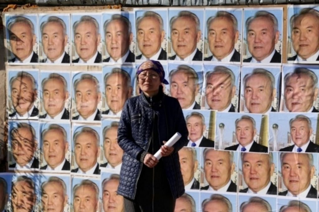 Woman standing outside her home plastered with images of the Kazakh president