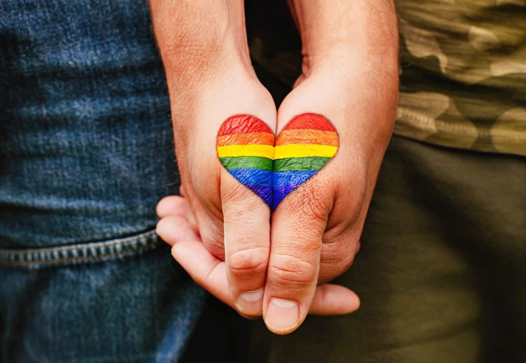 Rainbow heart drawing on hands.
