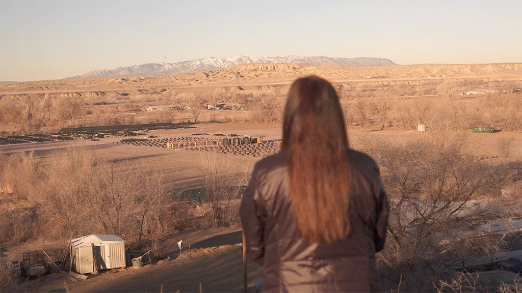 Bea Redfeather looks out at the top of a hill near her property in Shiprock, New Mexico