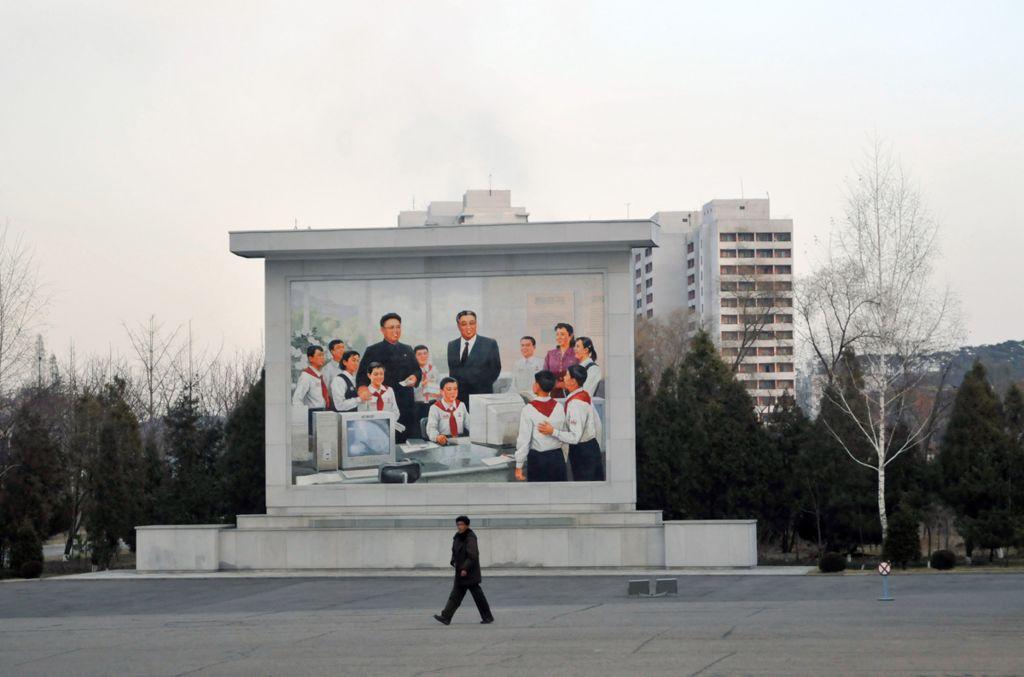 A mural depicts Kim Il-sung and Kim Jong-il in a school IT class