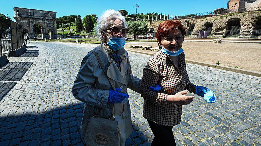 An elderly woman accompanied walking in Rome