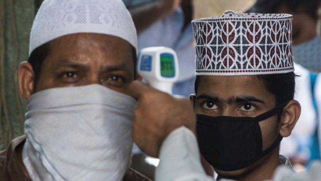Muslim men attending prayers having temperature checked