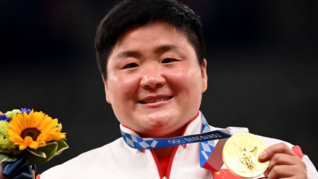 China's Gong Lijiao celebrates on the podium with her gold medal after wining the women's shot put event during the Tokyo 2020 Olympic Games at the Olympic Stadium in Tokyo on 1 August 2021.