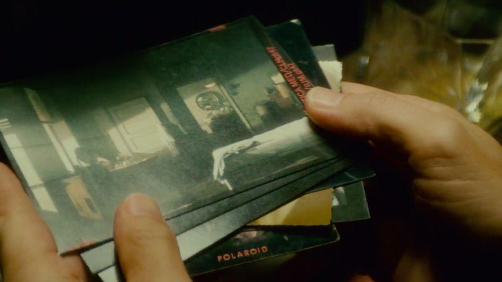 Deckard flicks through a set of Polaroid photographs