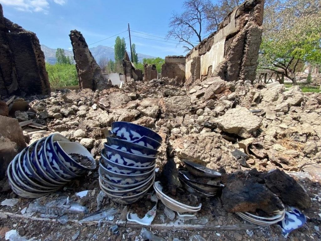 Some crockery is displayed near a home that has been reduced to rubble