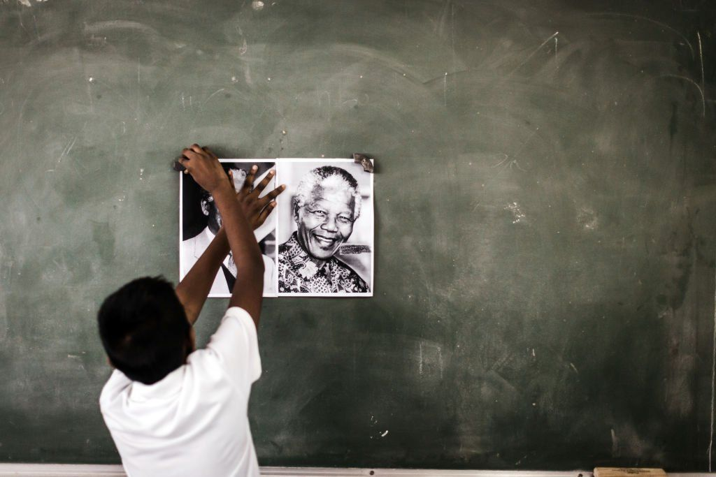 A child from Northlen Primary school sticks a poster of former South African President Nelson Mandela on the chalkboard in Durban on 18 July 2018
