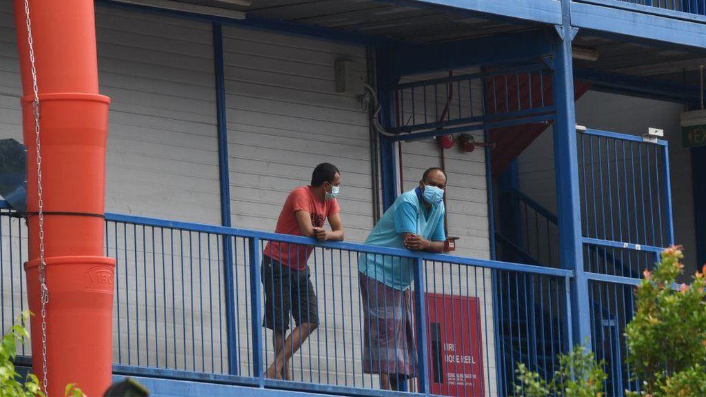 Рабочие-мигранты в масках для предотвращения распространения коронавируса COVID-19 выглядывают из здания общежития на карантине в Сингапуре 20 мая 2020 года.
