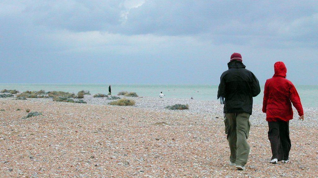 A couple stroll along the beach