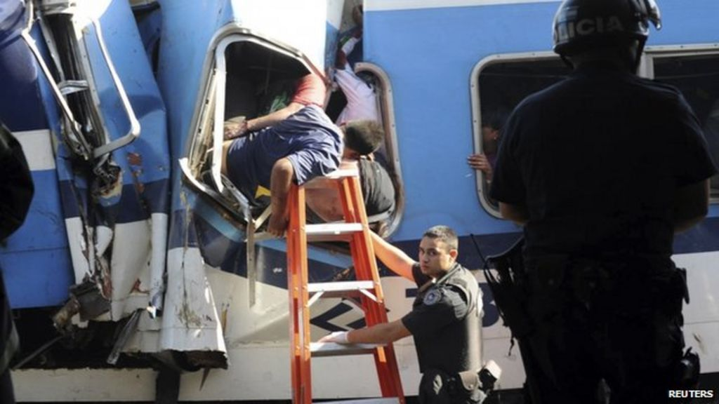 Rescue workers and policemen help an injured passenger after a train crashed at Once train station in Buenos Aires