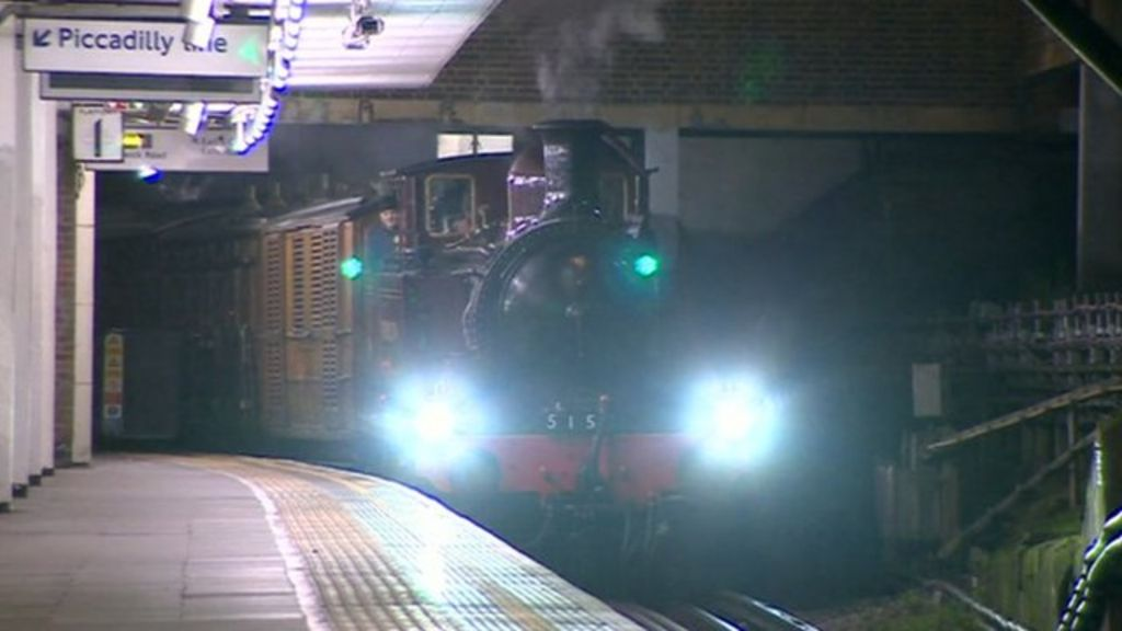 A steam engine pulling into a modern day tube station