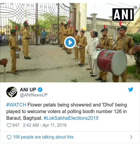 Twitter post by @ANINewsUP: #WATCH Flower petals being showered and 'Dhol' being played to welcome voters at polling booth number 126 in Baraut, Baghpat. #LokSabhaElections2019