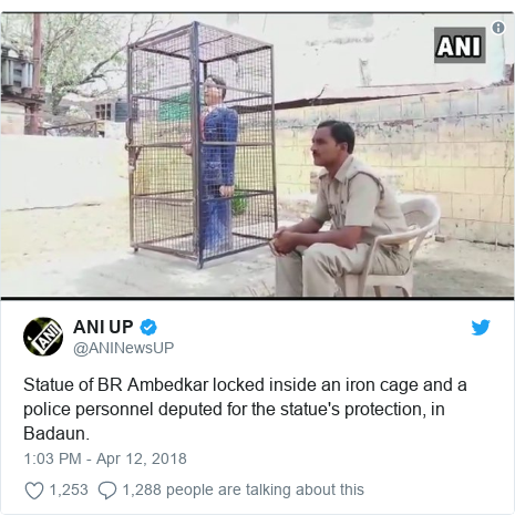 Twitter post by @ANINewsUP: Statue of BR Ambedkar locked inside an iron cage and a police personnel deputed for the statue's protection, in Badaun.
