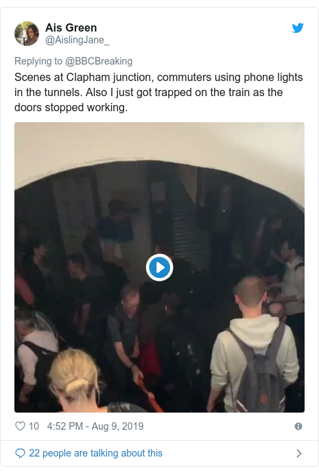 Twitter post by @AislingJane_: Scenes at Clapham junction, commuters using phone lights in the tunnels. Also I just got trapped on the train as the doors stopped working.