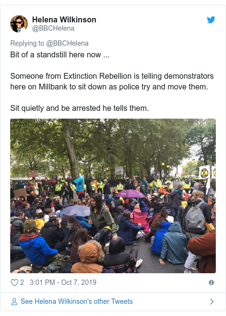 Twitter post by @BBCHelena: Bit of a standstill here now ...Someone from Extinction Rebellion is telling demonstrators here on Millbank to sit down as police try and move them. Sit quietly and be arrested he tells them.