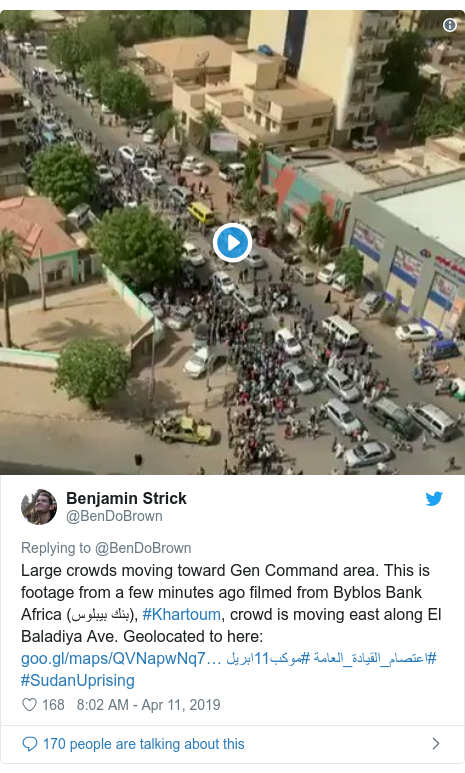 Twitter post by @BenDoBrown: Large crowds moving toward Gen Command area. This is footage from a few minutes ago filmed from Byblos Bank Africa (بنك بيبلوس), #Khartoum, crowd is moving east along El Baladiya Ave. Geolocated to here   #موكب11ابريل #اعتصام_القيادة_العامة #SudanUprising