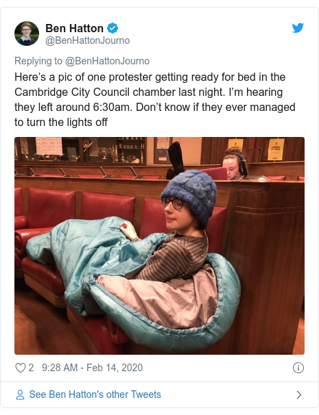 Twitter post by @BenHattonJourno: Here's a pic of one protester getting ready for bed in the Cambridge City Council chamber last night. I'm hearing they left around 6 30am. Don't know if they ever managed to turn the lights off