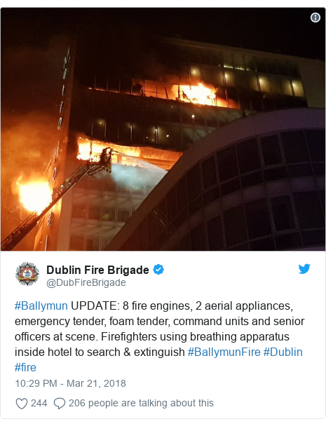 Twitter post by @DubFireBrigade: #Ballymun UPDATE  8 fire engines, 2 aerial appliances, emergency tender, foam tender, command units and senior officers at scene. Firefighters using breathing apparatus inside hotel to search & extinguish #BallymunFire #Dublin #fire