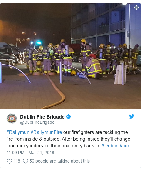 Twitter post by @DubFireBrigade: #Ballymun #BallymunFire our firefighters are tackling the fire from inside & outside. After being inside they'll change their air cylinders for their next entry back in. #Dublin #fire