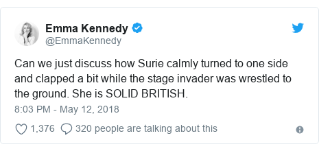 Twitter post by @EmmaKennedy: Can we just discuss how Surie calmly turned to one side and clapped a bit while the stage invader was wrestled to the ground. She is SOLID BRITISH.