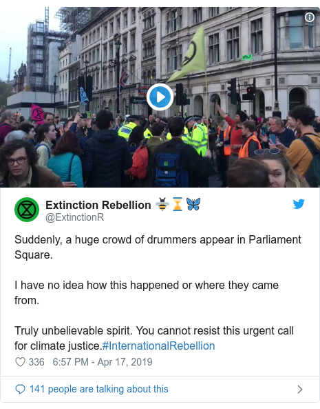 Twitter post by @ExtinctionR: Suddenly, a huge crowd of drummers appear in Parliament Square. I have no idea how this happened or where they came from.Truly unbelievable spirit. You cannot resist this urgent call for climate justice.#InternationalRebellion
