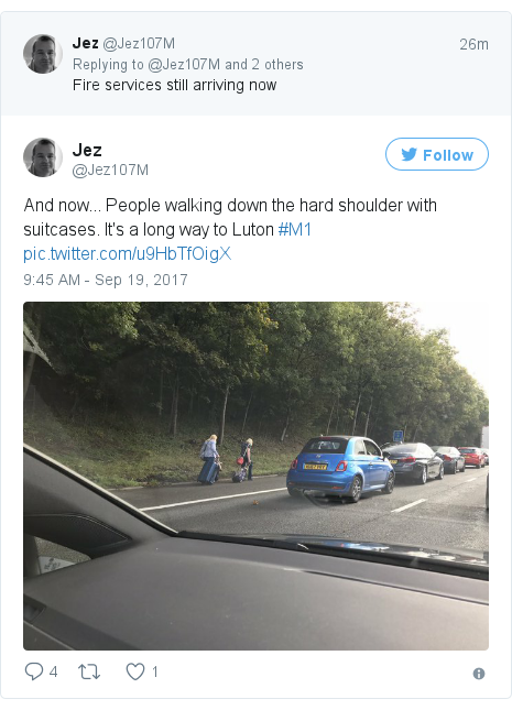 Twitter post by @Jez107M: And now...  People walking down the hard shoulder with suitcases. It's a long way to Luton #M1 pic.twitter.com/u9HbTfOigX